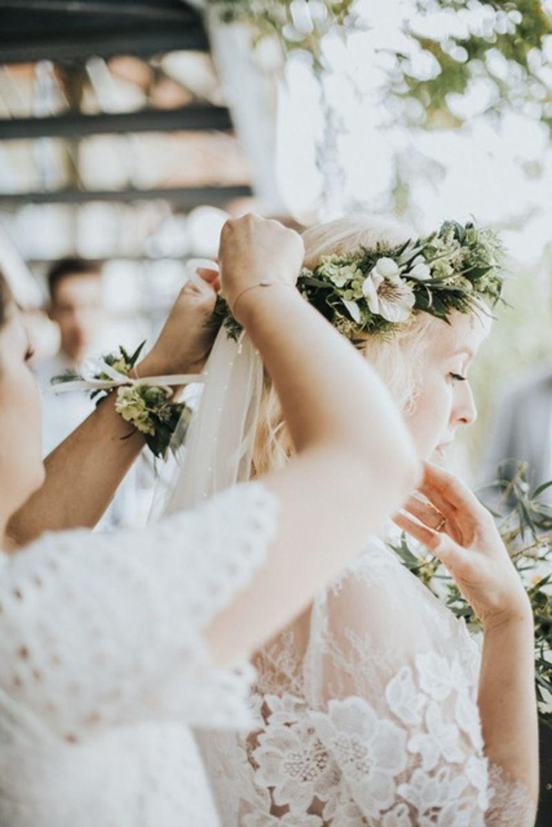 Trauzeugin legt der Braut einen Haarkranz an