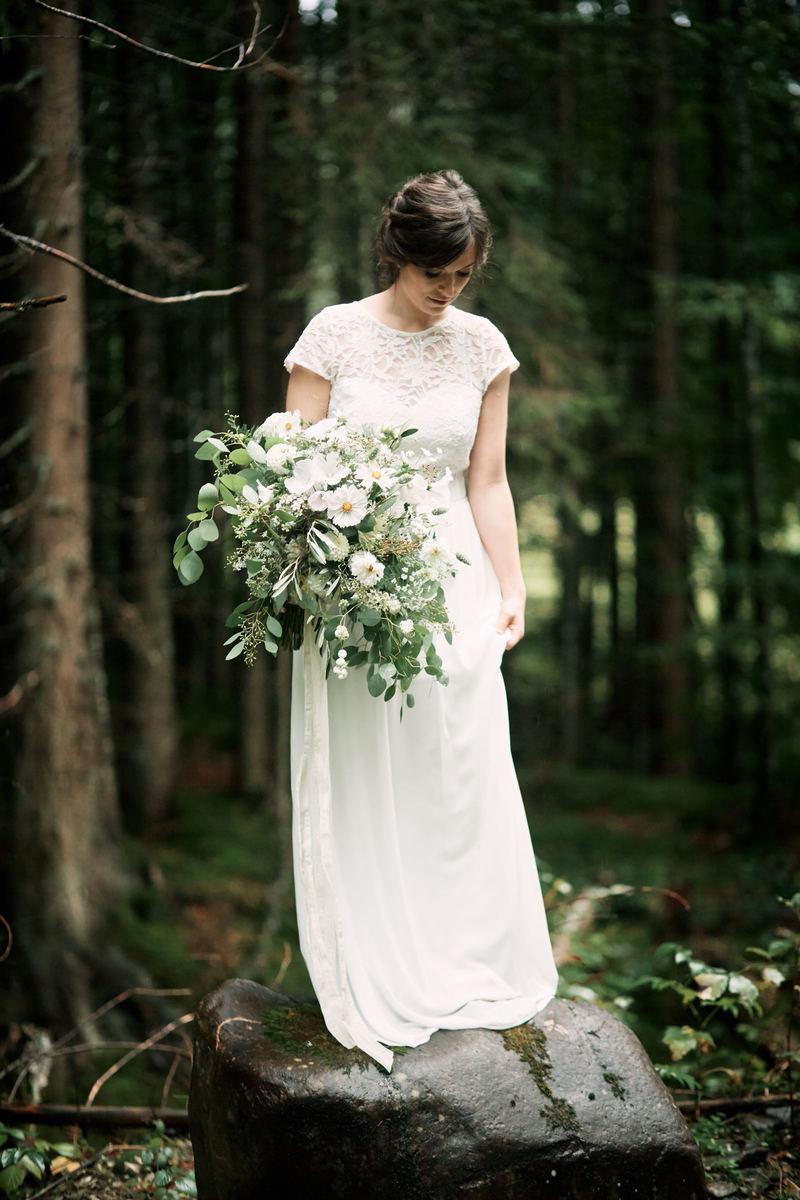Braut mit großem Brautstrauß und weißem Spitzenbrautkleid im Wald