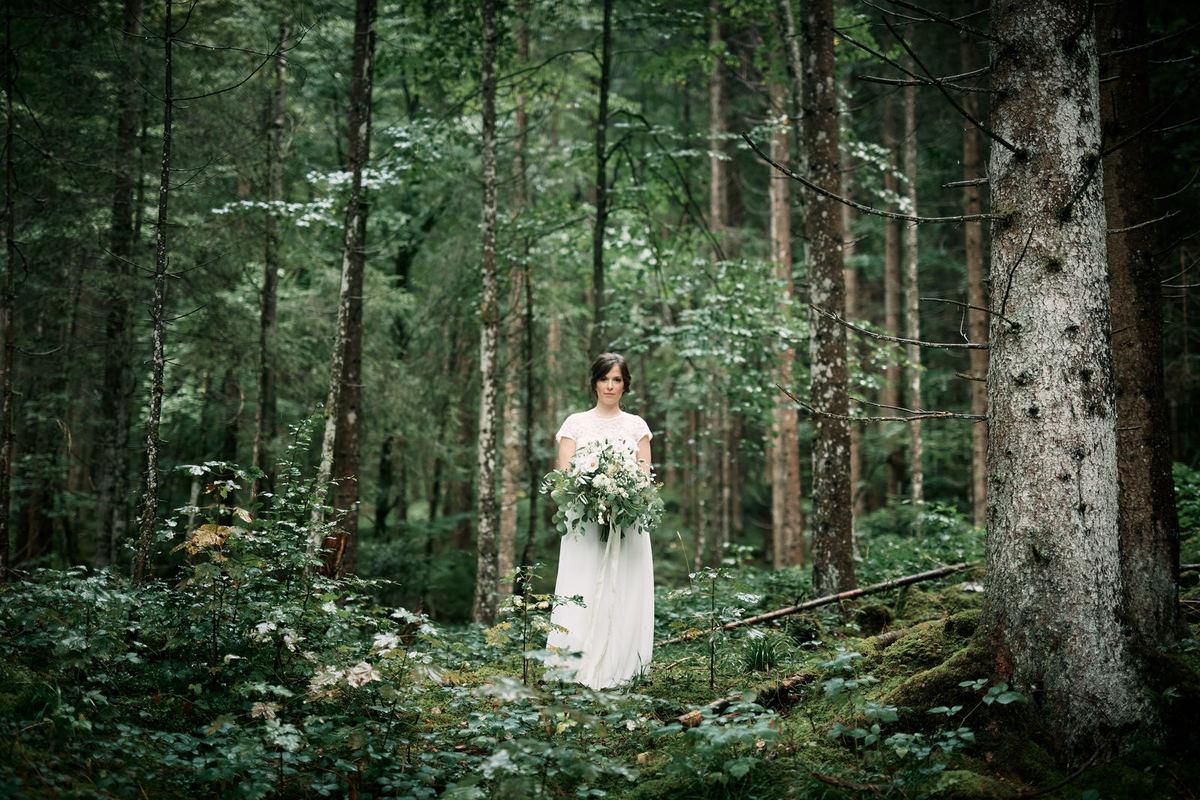 Braut im Wald hält Brautstrauß mit Eucalyptus für eien Sommerhochzeit