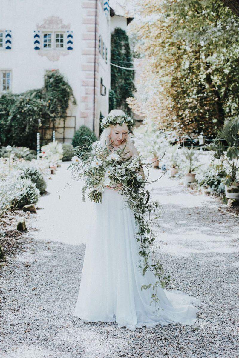 Braut bei Burg Schaubeck hält einen Oversized Brautstrauß mit Ästen