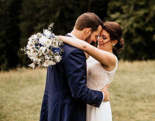Braut im Brautkleid mit Brautstrauß in blau und weiß umarmt Bräutigam