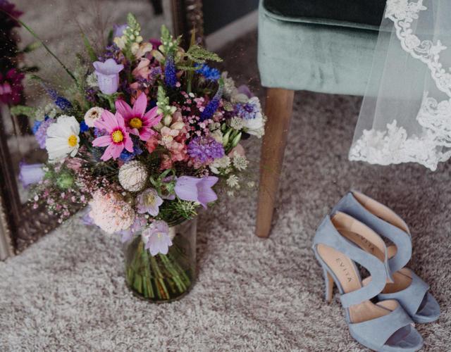 bunter wiesenhafter Sommerstrauß und die Schuhe der Braut