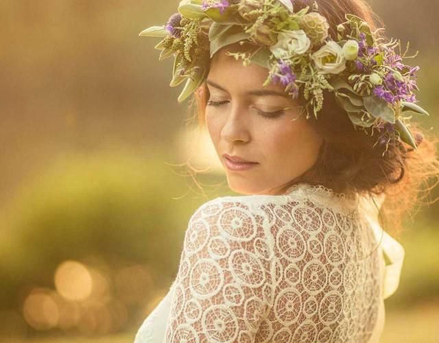 Braut trägt Brautkleid mit Spitze und einen großen Haarkranz