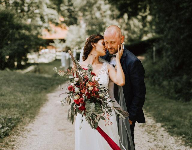 Braut mit Schleier hält Brautstrauß mit Federn und Eukalyptus