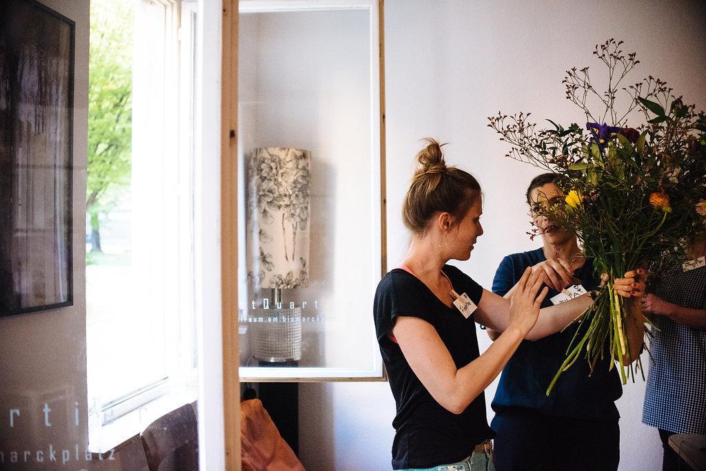 Friederike Paul von Wildflower Stuttgart erklärt die Details beim Binden eines Blumenstraußes